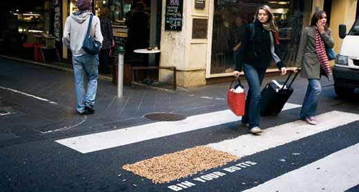 Сигаретные окурки, приклеенные на полоску пешеходного перехода